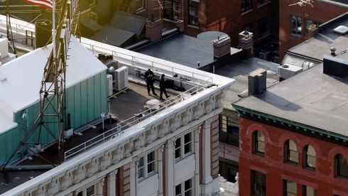 Police on a rooftop overlooking Boylston Street in Boston after the explosions. Photograph: Jessica Rinaldi/Reuters