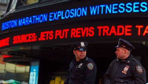 New York Police Department officers stand in the Times Square district of in New York underneath a news ticker displaying details from the fatal Boston marathon explosions. Photograph: Lucas Jackson/Reuters