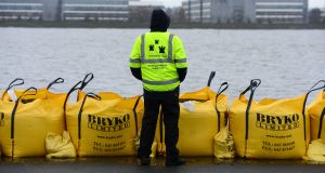 A Dublin City Council worker keeps watch on flood defence barriers along the Clontarf seafront as a very high tide poses a risk of flooding in December 2012. Photograph: Alan Betson/The Irish Times