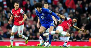 Everton's Marouane Fellaini  tussles with Arsenal's Mikel Arteta  during last night's clash at The  Emirates Staduim in  London.  Photograph: Adam Davy/PA