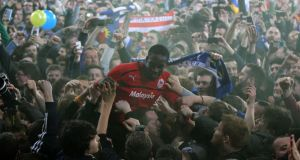 Cardiff City's Leon Barnett is carried by fans after last night's draw with Charlton Athletic was enough to see them promoted.