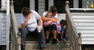 Neighbours of Boston Marathon explosion victim Krystle Campbell sit on the porch of her family home in Medford, Massachusetts yesterday. Photograph:  Brian Snyder/Reuters