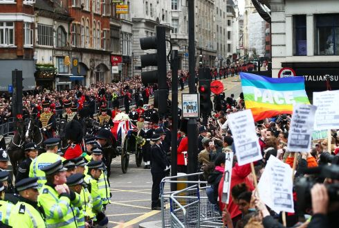 Protesters as the coffin is carried on a horse drawn gun carriage during the ceremonial funeral of former British prime minister Margaret Thatcher at Ludgate Hill. Photograph: Clive Rose/Getty Images