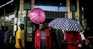 People take cover from an afternoon rain storm in downtown Harare, Zimbabwe. Photograph: Pete Muller/The New York Times