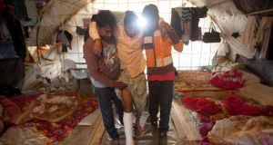 Bangladeshi worker Mohamed, 25, is helped by colleagues into a tent in the southwestern Greek town of Manolada yesterday following a shooting incident on Wednesday evening.  Photographs: Giorgos Moutafis/Reuters