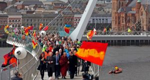 The Dalai Lama walks across the Peace Bridge during his visit to Derry. Photograph: Reuters