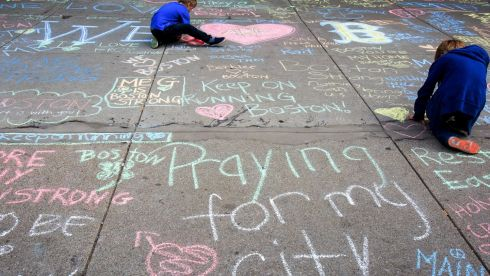 Children draw on an impromptu chalk memorial at Newbury Street, which runs parallel to Boylston Street, for those killed and injured in the Boston Marathon blasts. Photograph: Evan McGlinn/New York Times