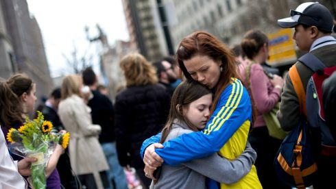 Tamera Clifton, of Portland, Oregon, who finished the Boston Marathon race before the explosions, hugs her daughter Aislin near a makeshift memorial on Boylston Street. Photograph: Gretchen Ertl/New York Times