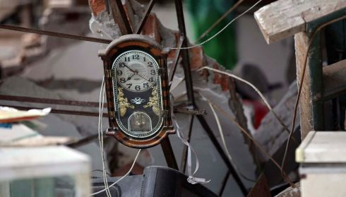 A clock amidst the debris of a collapsed house. Photograph: Reuters