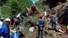 Rescuers try to remove rocks blocking a road after a strong earthquake in China's Sichuan province. Photograph: Reuters