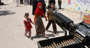 Children walk by a machinegun post near election centre in Baghdad today. Photograph: Wissm al-Okili/Reuters