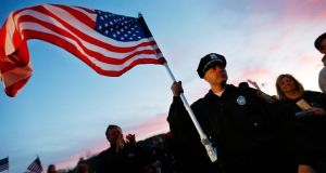 Watertown Police officer Brandon O'Neill holds an American flag during a candlelight vigil at Victory Park  in Watertown, Massachusetts last night. Photograph: Jared Wickerham/Getty Images