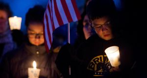 People hold candles during a vigil for slain MIT police officer Sean Collier at the Town Common in Wilmington, Massachusetts. Mr Collier, was shot multiple times in his car on Thursday night as Boston Marathon bombing suspects Dzhokhar Tsarnaev and his brother Tamerlan tried to evade capture. Photograph: Dominick Reuter/Reuters