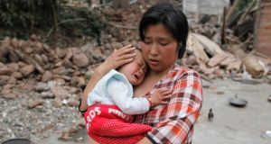 Survivor Chen Zhirong comforts her 18-month-old son next to debris at a village on the second day after an earthquake hit Longmen township of Lushan county, Sichuan province. Photograph: Jason Lee/Reuters