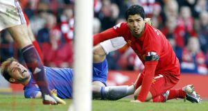 Liverpool's Luis Suarez (right) and Chelsea's Branislav Ivanovic (left) on the ground after Suarez appeared to bite Ivanovic at Anfield. Photograph: Peter Byrne/PA Wire.