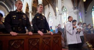 Boston police superintendents William Evans (left) and Kevin Buckley during Mass at the Cathedral of the Holy Cross to pray for those killed or injured in the Boston bombings, in Boston yesterday. Federal investigators, questioning the bombing suspect's motives, are reviewing a visit that one of them made to Chechnya and Dagestan last year. Photograph: Josh Haner/The New York Times