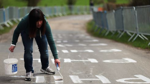 A race fan paints the road with the name of World Road Race Champion Philip Gilbert ahead of the 99th Liege-Bastogne-Liege cycle road race. Photograph: Bryn Lennon/Getty Images