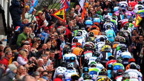 Crowds of people watch as the peloton climbs the Cote de Saint-Roch.  Photograph: Bryn Lennon/Getty Images