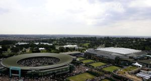Wimbledon's  Centre Court (right) with the roof on and Court One (left) at the All England Lawn Tennis and Croquet Club. Photograph: Rebecca Naden/PA Wire.