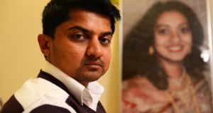 Praveen Halappanavar with a photograph of his late wife, Savita: there were deficiencies in her care but none is likely to have caused her death. Photograph: Cyril Byrne/Irish Times
