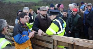 Border protest: Liam O'Mahony (left), chairman of the Great Southern Trail, and Cllr Denis Stack of Listowel, on either side of the barricade that Kerry farmers erected on the county boundary in protest against plans to extend the trail. Photograph: Jim McNamara