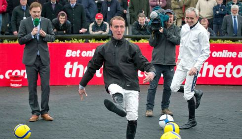 Jockey Robbie Power trys his hand at football before racing starts as comic Bernard O'Shea gives a running commentary. Photograph: Morgan Treacy/Inpho
