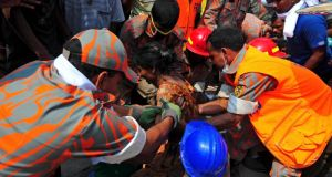 Rescue workers pull a garment worker alive from the rubble of the collapsed Rana Plaza building, in Savar today. Photograph:  REUTERS