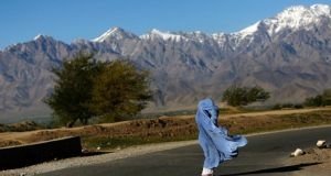 A woman in a burqa walks along a road on a windy day on the outskirts of the Afghan capital Kabul. Photograph: Mohammad Ismail/Reuters