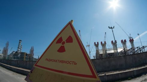 "A radiation warning sign in front of the containment shelter for the damaged fourth reactor (left) and the new safe confinement structure (right) at the Chernobyl nuclear power plant, photographed on April 23rd, 2013, three days ahead of the 27th anniversary of the disaster at the plant. The confinement structure, being placed over the existing Chernobyl ""sarcophagus"", will have a span of 247 meters and weigh 29,000 tonnes when fully assembled, according to the European Bank of Reconstruction and Development. Photograph:  Photograph: Gleb Garanich/Reuters"