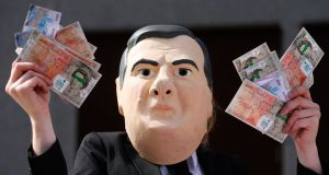 A demonstrator wearing a mask, depicting Britain's chancellor  George Osborne, holds up fake bank notes outside the Barclays Bank AGM earlier this week. Photograph: Andrew Winning/Reuters