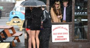 Racegoers  shelter under an umbrella during a hail shower at Punchestown races yesterday. Photograph: Cyril Byrne
