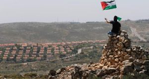 A protester waves a Palestinian flag in front of the Jewish settlement of Ofra during clashes near the West Bank village of Deir Jarir near Ramallah. Israeli soldiers fired tear gas and rubber bullets to disperse about 500 Palestinian villagers marching toward a Jewish settlement outpost in the occupied West Bank yesterday. Photograph: Mohamed Torokman/Reuters