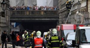 Firefighters search the immediate area and onlookers gather after a large explosion this morning in Prague, Czech Republic.  Photograph: David W Cerny/Reuters