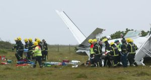 Firemen take two of the casualties from the aircraft at Inverin. Photograph: Joe O'Shaughnessy