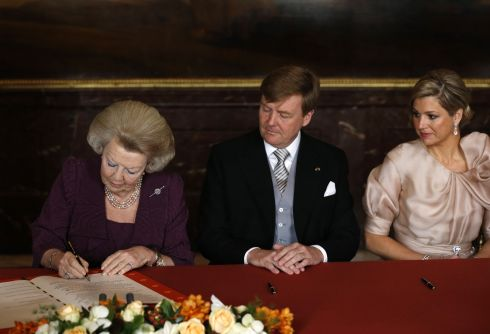 Queen Beatrix of the Netherlands (L) signs her name to the Act of Abdication as her son Prince Willem-Alexander of the Netherlands and his wife Princess Maxima of the Netherlands watch. Photograph: Bart Maat/ Pool/Getty Images