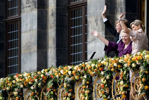 Princess Beatrix of the Netherlands, her son King Willem-Alexander and his wife Queen Maxima wave to the crowd at the Royal Palace balcony. Photograph: Robin Utrecht/Reuters