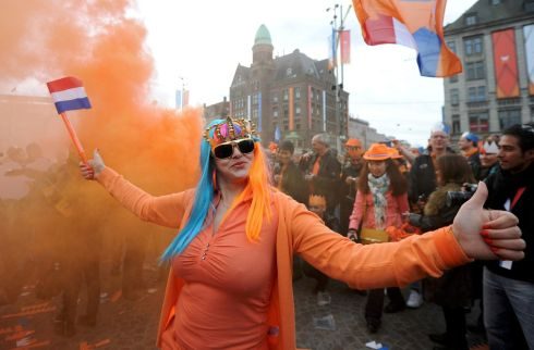 A woman wearing orange, the royal colour, celebrates the new King Willem-Alexander. Photograph: Laurent Dubrule/Reuters