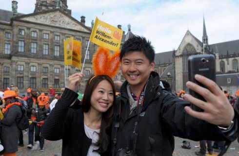 A couple take pictures of themselves as they celebrate the new King Willem-Alexander in Amsterdam's Dam Square. Queen Beatrix of the Netherlands abdicated on Tuesday, handing over to her eldest son, who became the first King of the Netherlands in over 120 years. Photograph: Laurent Dubrule/Reuters