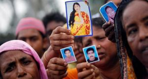 Relatives show pictures of garment workers who are missing, during a protest over the collapse of the Rana Plaza building, in Savar, outside Dhaka. Photograph: Andrew Biraj/Reuters