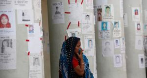 A woman waits for news of her relative, a garment worker, who is still missing after the collapse of Rana Plaza building, in front of missing people posters in Savar, outside Dhaka. Photograph: Andrew Biraj/Reuters