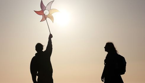 A person holds a holds a windmill as people watch the sun rise as they join in a May Day  dawn celebration service in Glastonbury, England. Photograph: Getty Images