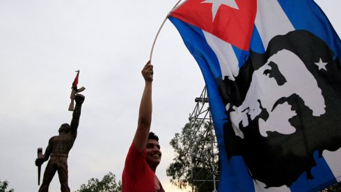 "A supporter of the ruling Sandinista party holds up a Cuban national flag with the image of revolutionary leader Ernesto ""Che"" Guevara during early May Day celebrations in Managua Photograph: Reuters"