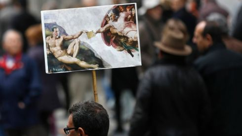 A man holds a placard depicting Spain's prime minister Mariano Rajoy and former People's Party treasurer Luis Barcenas inspired by Michelangelo Buonarroti's painting 'The Creation of Adam' during a May Day protest in Madrid today. Photograph: Reuters