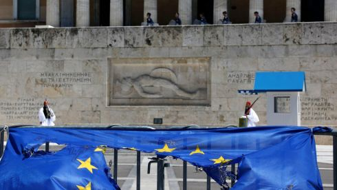 Presidential guards and riot police are seen by a burned EU flag in front of the Tomb of the Unknown Soldier in Athens following a May Day rally. Photograph: Reuters