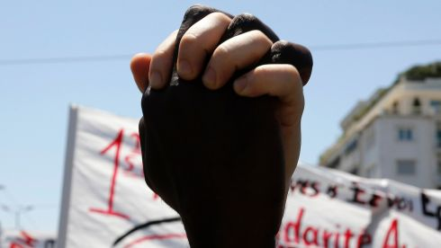 An African immigrant holds hands with a Greek protester in solidarity during a May Day rally in Athens today. Photograph: Reuters