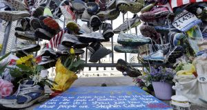 Running shoes hang on a fence at a makeshift memorial near the Boston Marathon finish line in Boston's Copley Square.