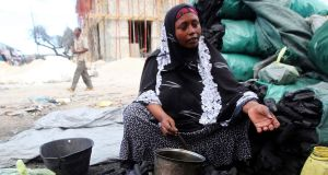 A woman sells charcoal along a street near Bakara market in Mogadishu. Photograph: Ismail Taxta/Reuters