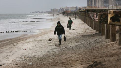 People walk by the remaining pilings of the of the Rockaway boardwalk. Photograph: Spencer Platt/Getty Images