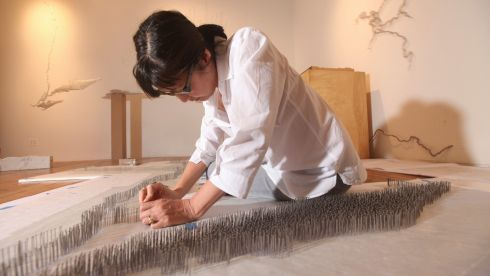"Maya Lin, an architect and artist, works on her ""Pin River ? Hudson"" piece at her studio in New York. After Hurricane Sandy, Lin decided her new show at Pace Gallery would fix on the Manhattan borough of New York and its surrounding landscape, environmental history and waterways.  Photograph: Chester Higgins Jr./The New York Times"
