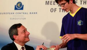 President of the European Central Bank Mario Draghi signs the newly introduced €5  banknote for a school boy after an ECB news conference  in Bratislava today. Photograph: Petr Josek /Reuters